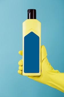 Ręka w gumowej żółtej rękawicy zawiera butelkę płynnego detergentu