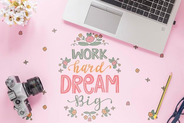 Rocznik kamery laptop i motywacyjna wiadomość na biurku