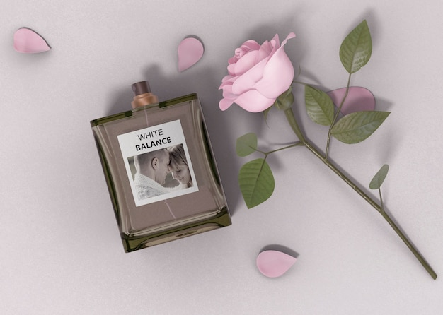 Róża obok butelki perfum na stole