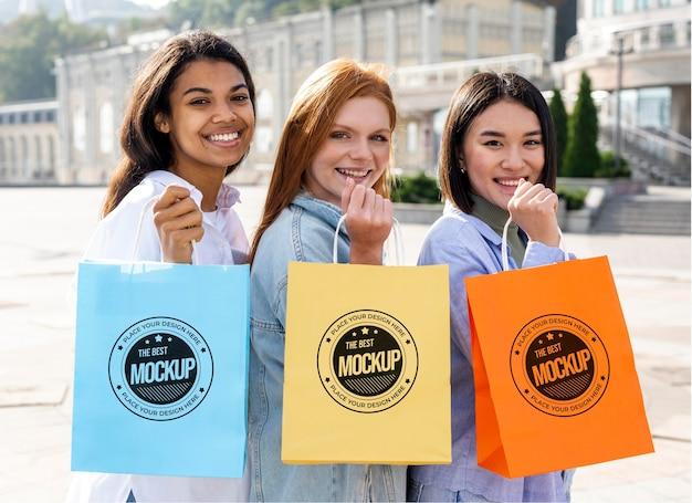 Różne piękne kobiety trzymając makiety torby na zakupy