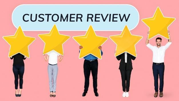 Różnorodni biznesmeni pokazuje złotych gwiazdowych ocen symbole