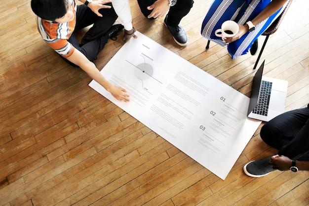 Różnorodni ludzie przeprowadzają burzę mózgów w warsztacie na papierowej makiecie