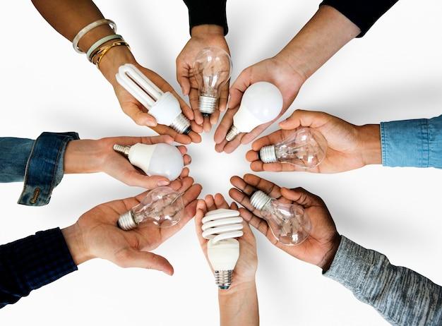 Różnorodność ręce trzyma energię żarówka innowacji