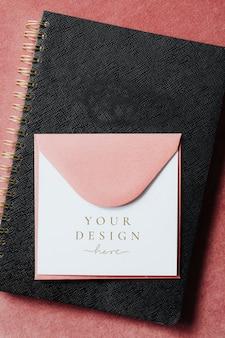 Różowa makieta koperty na czarnym zeszycie
