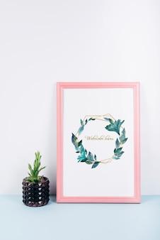Różowa makieta ramowa z dekoracyjnym kaktusem