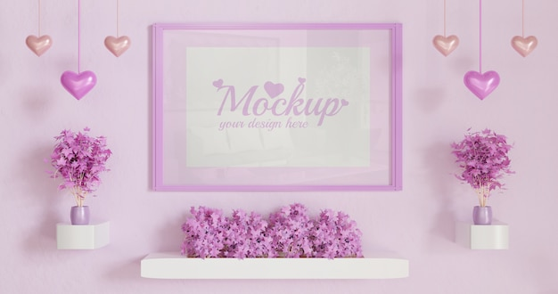 Różowa ramka pionowa na różowym kolorze ściany z kilkoma różowymi roślinami liściastymi na białej ścianie biurka