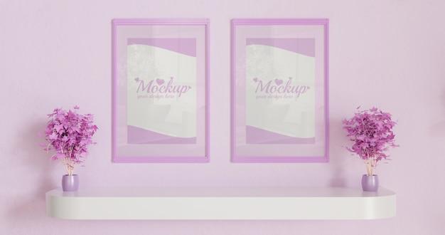 Różowe poziome ramki na różowej ścianie z różowymi roślinami liściastymi na białej ścianie biurka