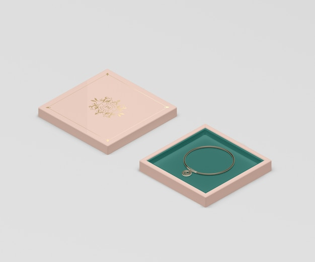 Różowe pudełko na biżuterię z małą złotą bransoletką