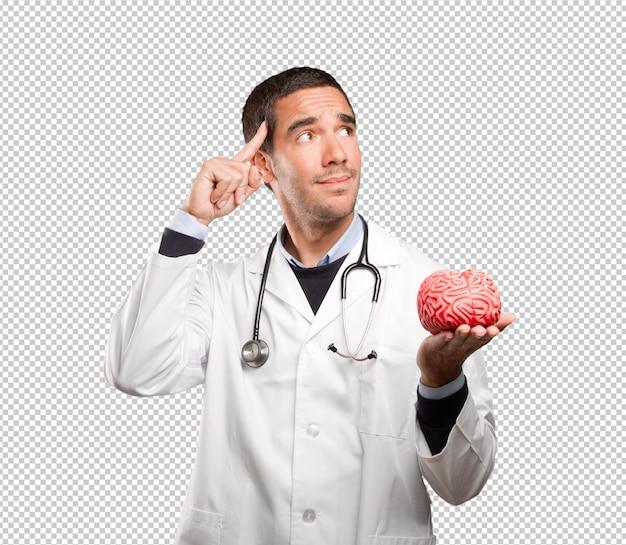 Rozważna doktorska mienie zabawkarski mózg przeciw białemu tłu