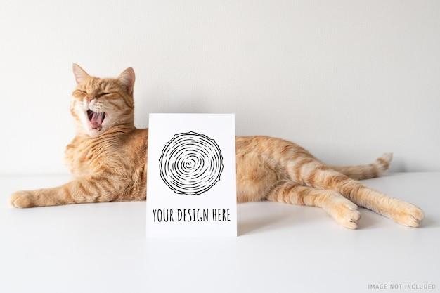 Rudy kot ziewający z makietą pionowej pocztówki
