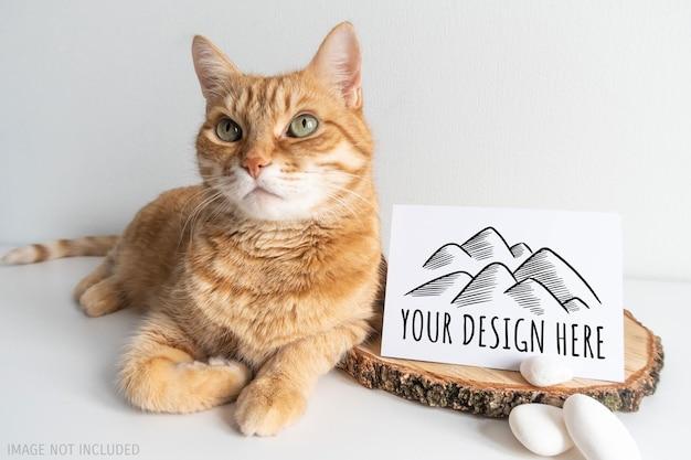 Rustykalny makiety pocztówki imbirowego kota. karta pozioma z białym kamykiem na makieta tło biały stół. słodkie zwierzę domowe z miejscem na twój obraz lub tekst. do projektów makramy i rękodzieła