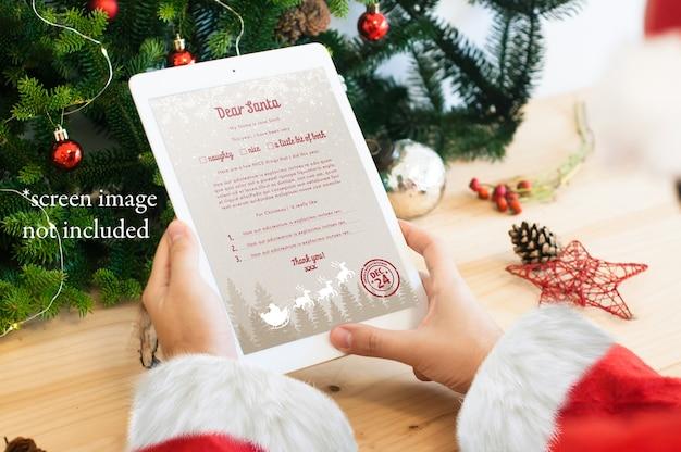 Santa czytający cyfrowy list na makiecie tabletu