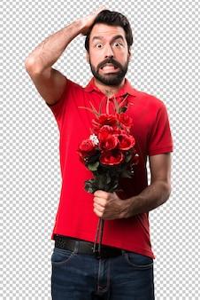 Sfrustrowany przystojny mężczyzna trzyma kwiaty