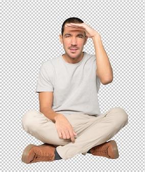 Skoncentrowany młody człowiek z gestem odwracania wzroku