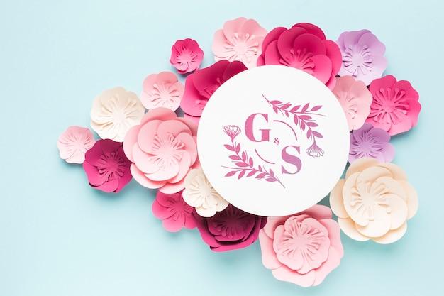 Ślubna makieta monogramu z papierowymi kwiatami na niebieskiej tapecie