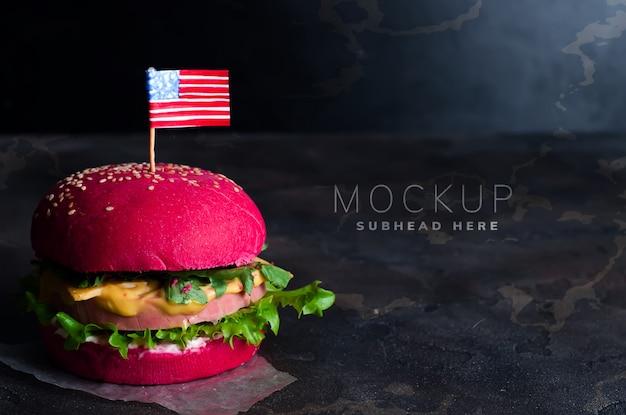 Smaczny hamburger z małymi amerykańskimi flagami na kamieniu
