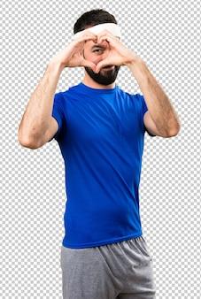 Śmieszny sportowiec robi sercu z jego rękami