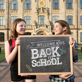 Smiley dziewczyny trzyma blackboard egzamin próbnego