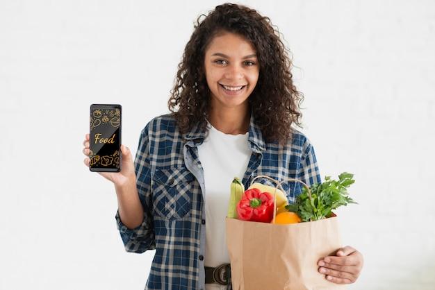 Smiley kobieta z telefonem i warzywami