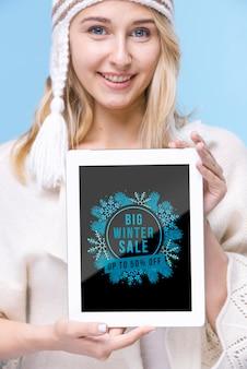 Smiley młoda kobieta trzymając tabletkę