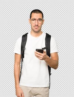 Smutny student korzystający z telefonu komórkowego
