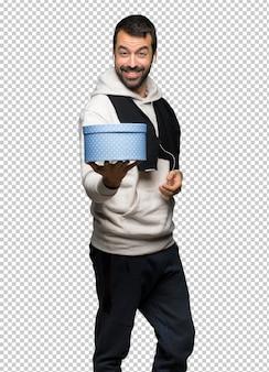 Sportowy mężczyzna trzyma prezent w rękach