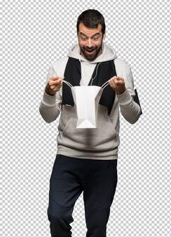 Sportowy mężczyzna zaskakujący podczas gdy trzymający mnóstwo torba na zakupy
