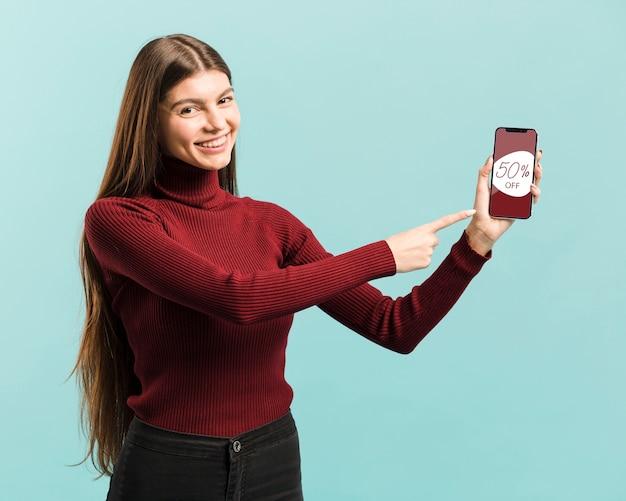 Średni strzał szczęśliwa dziewczyna wskazuje na jej telefon