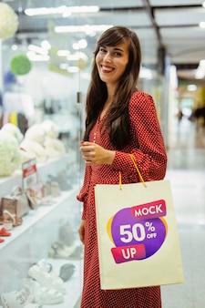 Średnio strzał uśmiechnięta kobieta trzyma torbę