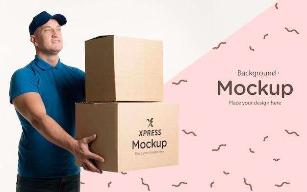 Średnio strzałowy mężczyzna trzyma makietę niektórych pudełek