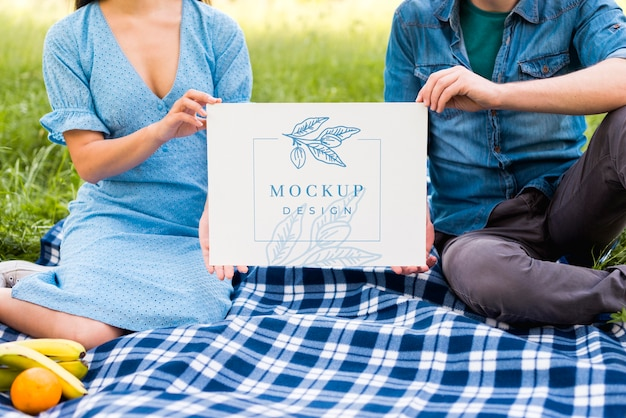 Średnio ujęcie pary trzymającej makietę piknikową