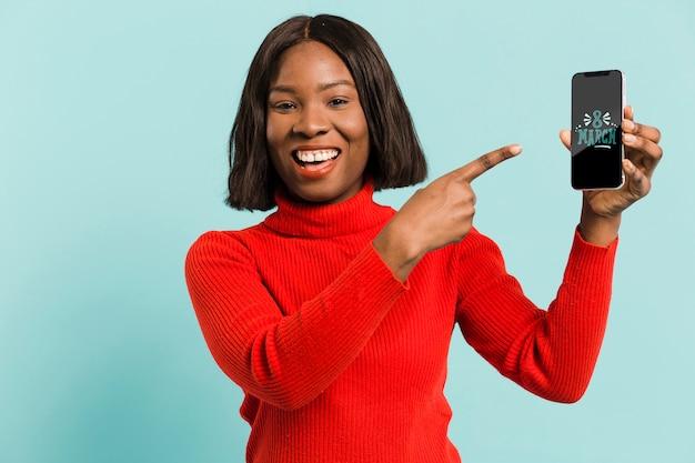Środek strzelał smiley kobiety trzyma smartphone