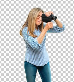Starsza piękna kobieta z rocznika kinową kamerą