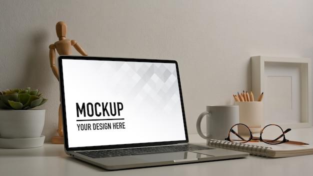 Stół roboczy z makietą laptopa, okularami i dekoracjami w pokoju biurowym
