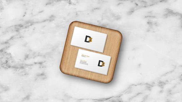 Stos wizytówek na makiecie na pokładzie drewna na białym tle