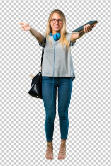 Studencka dziewczyna przedstawia okulary i zaprasza przychodzić z ręką. cieszę się, że przyszedłeś