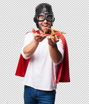 Super bohater trzyma zabawkowy samolot