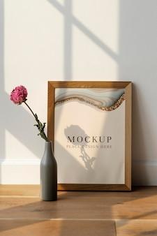 Suszony kwiat różowej piwonii w szarym wazonie przy makiecie drewnianej ramy