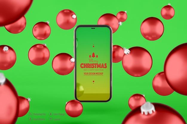 Świąteczna kula i mobilna makieta na białym tle na zielonym tle