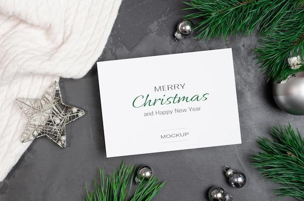 Świąteczna makieta z życzeniami ze srebrnymi świątecznymi dekoracjami i gałęziami sosny