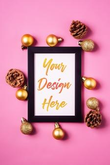 Świąteczna minimalna kompozycja z pustą ramką na zdjęcia ze złotymi ozdobami i szyszkami d