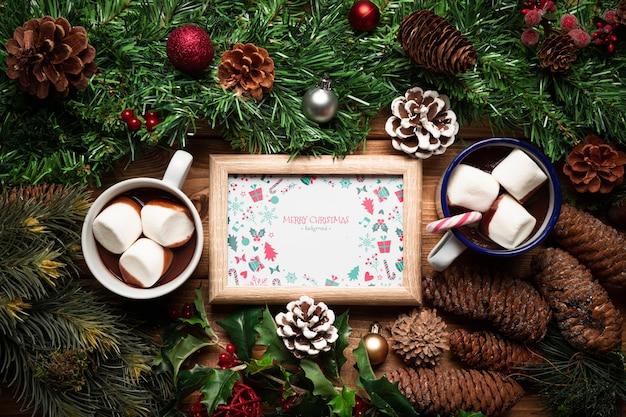 Świąteczne dekoracje sosnowe i gorące czekoladki z makietą ramy