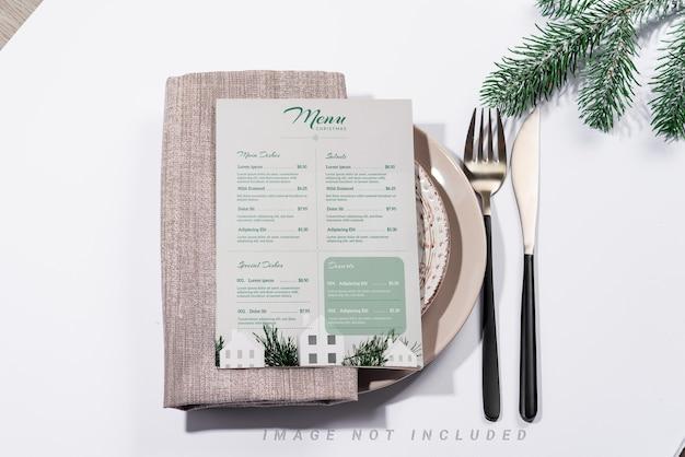 Świąteczne nakrycie stołu ze sztućcami i makietą białej broszury na stole.