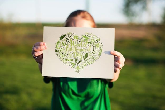 Światowy dzień środowiska makieta z wolontariuszem trzyma papier