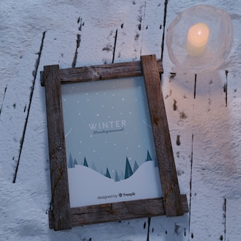 Świeca obok ramki z motywem zimowym