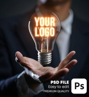 Świecąca żarówka unosząca się na makiecie logo ręka biznesmena