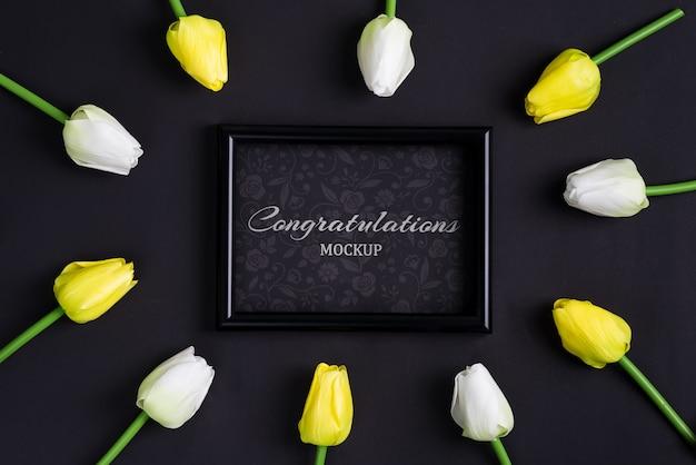 Świeże białe i żółte tulipany z czarną ramką na zdjęcia