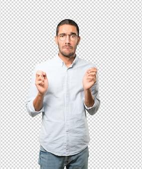 Szalony młody człowiek robi nerwowy gest