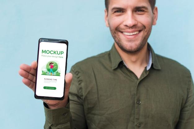 Szczegół uśmiechnięty mężczyzna trzyma smartfon