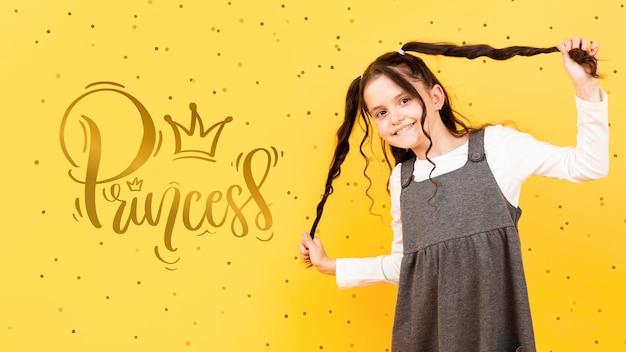 Szczęśliwa dziewczyna pozuje podczas gdy chwytający jej ponytails